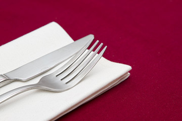 Knife and fork with white napkin on red tablecloth