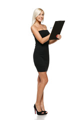 Full length of smiling woman making notes on the tablet