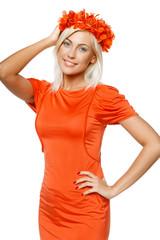 Smiling woman in orange dress holding wreath on head