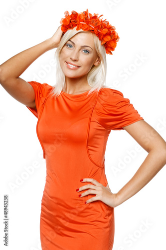 Smiling woman in orange dress holding wreath on head