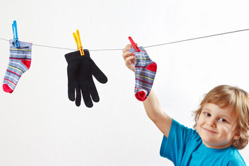 Little boy hanging your glove and socks on a white background