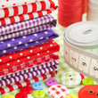 Buttons, colorful fabrics, measuring tape, pin cushion, thimble