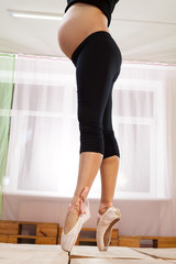 Lower half waist down image of young pregnant woman on pointe