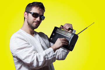 Young bearded man holding a vintage radio