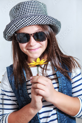 Attractive young girl in cap with a flower in hands
