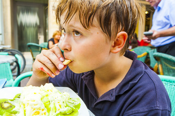 child is eating icecream at  a outdoor table