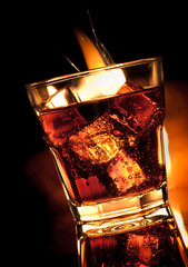 cola with whiskey in glass and fire on black