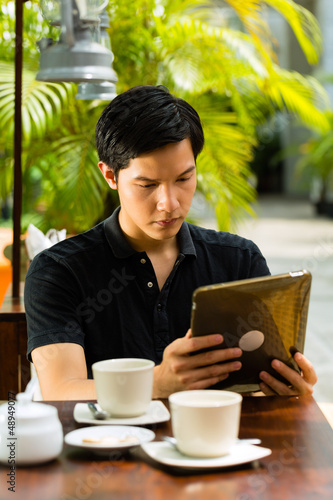 Asian man is sitting in a bar or cafe outdoor