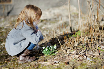 Little toddler girl touching flowers
