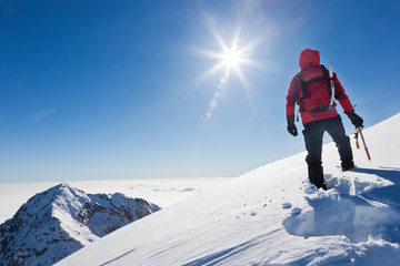 Mountaineer reaches the top of a snowy mountain in a sunny winte