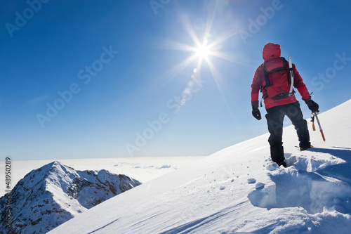 Foto op Canvas Wintersporten Mountaineer reaches the top of a snowy mountain in a sunny winte