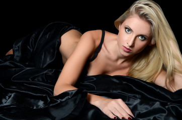 The beautiful girl the blonde on a black bed