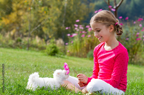 Happy girl with cute puppy in the garden