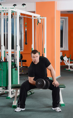 man with dumbbells in sports club