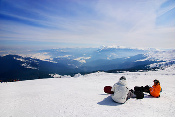 snowboarders sitting on anow and see at mountains