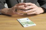 Mann mit Geldstapel auf Tisch