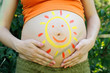 Pregnant woman abdomen with drawing sun.