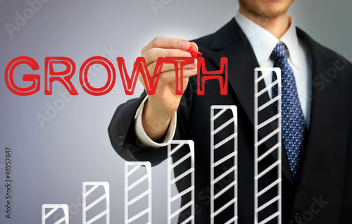 Businessman writing growth over a bar graph
