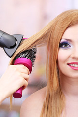 Beautiful woman and hands with hairdryer in beauty salon