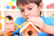Cute little boy makes birdhouse for birds