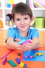 Cute little boy holding plasticine over desk