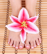 manicured bare feet with lily flower over bamboo mat