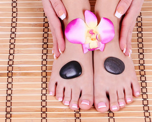 foot care, feet and hands with french manicure on bamboo mat