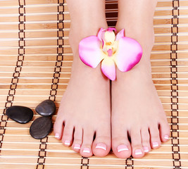 beautiful manicured feet with orchid flowers over bamboo mat