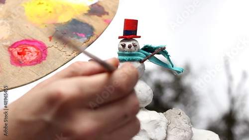 man painting buttons on a snowman miniature