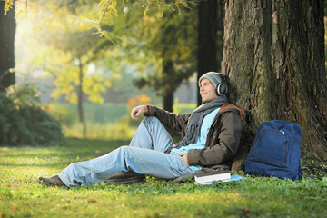 A male student relaxing and listening music seated in the park