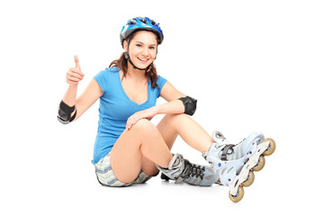 A smiling girl with roller skates giving a thumb up