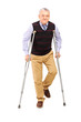 Full length portrait of a happy gentleman walking with crutches