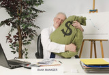 Bank Manager Hugging Bag Of Money