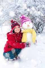 Little girl and snowman