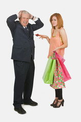 Woman Handing Credit Card To Frustrated Man