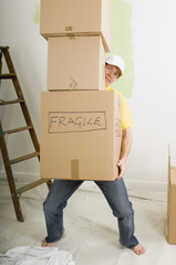 man carrying many heavy moving boxes