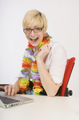 Very Happy Woman Sitting At Desk Wearing A Lei