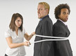 Woman Tying Two Businessmen Together With A Rope