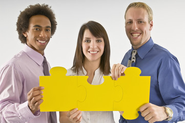 A group of business people holding puzzle pieces