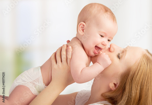 Happy  young mother kissing a baby
