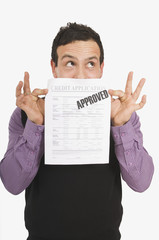 Man Holding Approved Credit Application