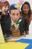 Businessman Blowing Out Birthday Candles