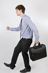 Young Businessman Walking With Briefcase In His Hand