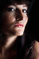 Beautiful young woman in black hat with net