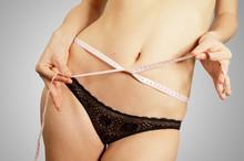 Junge Frau, die ihre Taille nach einer Diät