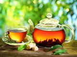 Fototapeta Kawa jest smaczna - Cup of tea and teapot. © volff