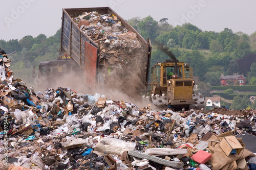 A bulldozer and garbage truck on a landfill waste site