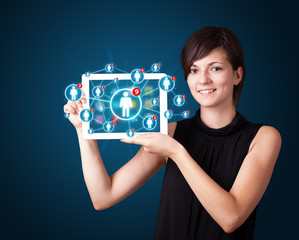 young woman holding tablet with social network icons