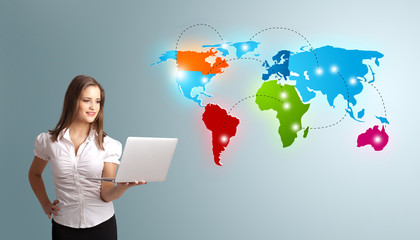 Young woman holding a laptop and presenting colorful world map