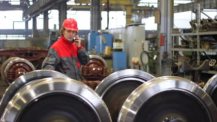 Worker controls wheels of rail vehicles in factory